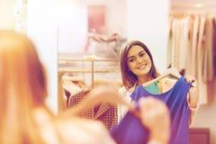 Mujer feliz con ropa en el espejo de la tienda de ropa Imágenes de archivo libres de regalías