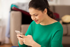 Mujer feliz con smartphone en casa Fotos de archivo libres de regalías