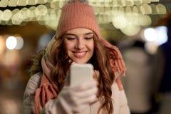 Mujer feliz con smartphone en la Navidad Fotografía de archivo libre de regalías