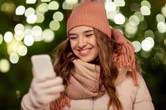 Mujer feliz con smartphone en la Navidad Imagenes de archivo