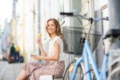 Mujer feliz con smartphone, la bici y el helado Foto de archivo