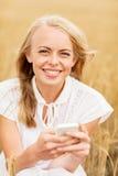 Mujer feliz con smartphone y los auriculares Imágenes de archivo libres de regalías
