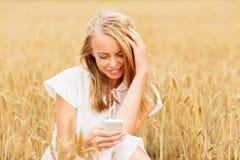 Mujer feliz con smartphone y los auriculares Foto de archivo libre de regalías