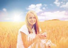 Mujer feliz con smartphone y los auriculares Imagen de archivo