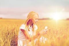 Mujer feliz con smartphone y los auriculares Foto de archivo