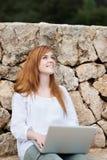 Mujer feliz con su ordenador portátil en el jardín Imagen de archivo