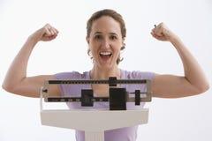 Mujer feliz con sus resultados de la escala - aislados Fotos de archivo libres de regalías