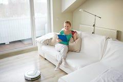 Mujer feliz con té de consumición de la PC de la tableta en casa imágenes de archivo libres de regalías