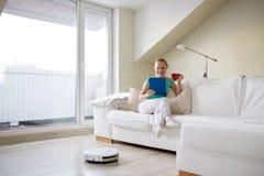 Mujer feliz con té de consumición de la PC de la tableta en casa fotografía de archivo libre de regalías