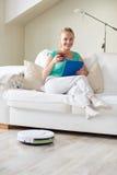 Mujer feliz con té de consumición de la PC de la tableta en casa Foto de archivo