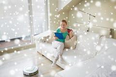 Mujer feliz con té de consumición de la PC de la tableta en casa Fotografía de archivo