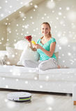 Mujer feliz con té de consumición del smartphone en casa Fotografía de archivo