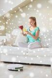 Mujer feliz con té de consumición del smartphone en casa Fotos de archivo