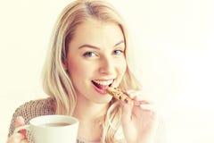 Mujer feliz con té que come la galleta en casa Fotos de archivo