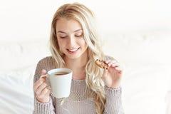 Mujer feliz con té y galletas en cama en casa Imagen de archivo libre de regalías