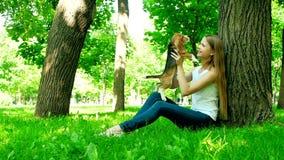 Mujer feliz con un beagle del perro que juega en la naturaleza almacen de video