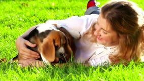 Mujer feliz con un beagle del perro que juega en la naturaleza metrajes