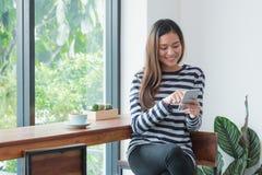 Mujer feliz de Asia que usa la ventana cercana móvil en el restaurante del café, empuje Fotografía de archivo libre de regalías