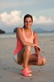 Mujer feliz de la aptitud antes de entrenar en la playa fotos de archivo