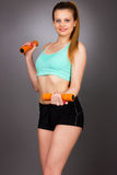 Mujer feliz de la aptitud con la elaboración de las pesas de gimnasia foto de archivo libre de regalías