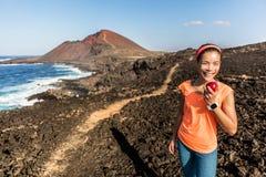Mujer feliz de la aptitud en pista de senderismo que come la manzana Foto de archivo libre de regalías
