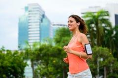 Mujer feliz de la aptitud que corre en el parque de la ciudad Fotografía de archivo