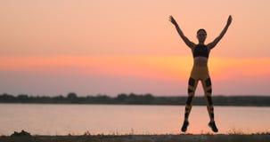 Mujer feliz de la aptitud que hace ejercicio del salto de los enchufes o de la estrella de salto en la playa al aire libre, espac almacen de metraje de vídeo