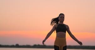 Mujer feliz de la aptitud que hace ejercicio del salto de los enchufes o de la estrella de salto en la playa al aire libre, espac metrajes