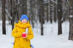 Mujer feliz de la belleza que toma el sol en el invierno una bebida caliente Imagen de archivo