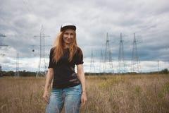 Mujer feliz de la energía joven que se coloca en la cámara en campo amarillo con los pilones del poder Imagen de archivo