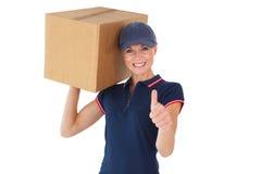 Mujer feliz de la entrega que sostiene la caja de cartón que muestra los pulgares para arriba Fotos de archivo libres de regalías