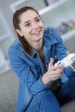 Mujer feliz de la imagen con la palanca de mando que juega a los videojuegos Imagen de archivo libre de regalías
