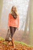 Mujer feliz de la moda con el bolso en parque del otoño Fotos de archivo