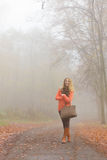 Mujer feliz de la moda con el bolso en parque del otoño Fotografía de archivo
