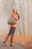 Mujer feliz de la moda con el bolso en parque del otoño Imagen de archivo
