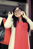 Mujer feliz de la moda con los panieres que invita al teléfono móvil Foto de archivo libre de regalías