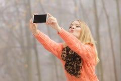 Mujer feliz de la moda en el parque que toma la foto del selfie Fotos de archivo