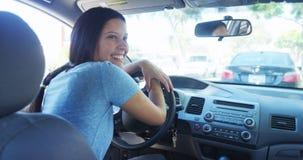 Mujer feliz de la raza mixta que se sienta en esperar del coche Foto de archivo libre de regalías