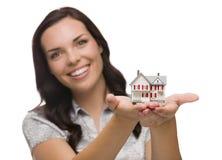 Mujer feliz de la raza mixta que sostiene la pequeña casa aislada en blanco fotografía de archivo