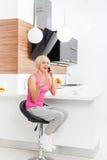 Mujer feliz de la sonrisa que usa la tabla que se sienta de la llamada de teléfono Imagen de archivo