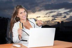 Mujer feliz de las compras en línea en la oficina usando su tarjeta de crédito Imágenes de archivo libres de regalías