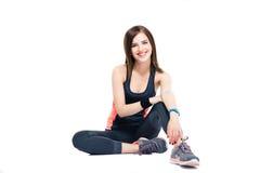 Mujer feliz de los deportes que se sienta en el piso Imagen de archivo libre de regalías