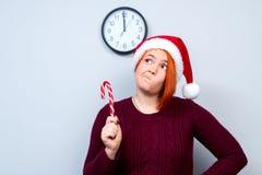 Mujer feliz del Año Nuevo de la Navidad en el sombrero de Santa Claus con el sti del caramelo Imagenes de archivo