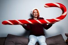 Mujer feliz del Año Nuevo de la Navidad en el sombrero de Santa Claus con el sti del caramelo Foto de archivo
