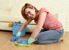 Mujer feliz del ama de casa con el arrodillamiento del piso de la sonrisa que se lava de la casa hermosa de la limpieza Fotografía de archivo libre de regalías