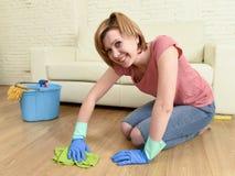 Mujer feliz del ama de casa con el arrodillamiento del piso de la sonrisa que se lava de la casa hermosa de la limpieza Imagenes de archivo