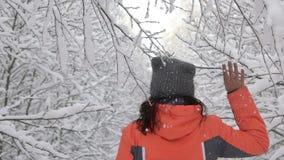 Mujer feliz del día de invierno que camina en la rama conmovedora de árboles, nieve del bosque nevoso blanco de maderas que cae d almacen de video