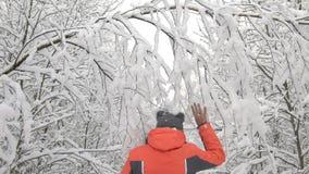 Mujer feliz del día de invierno que camina en la rama conmovedora de árboles, nieve del bosque nevoso blanco de maderas que cae d metrajes