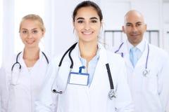 Mujer feliz del doctor con el personal médico en el hospital Imagen de archivo libre de regalías