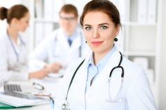 Mujer feliz del doctor con el personal médico en el hospital que se sienta en la tabla Fotografía de archivo